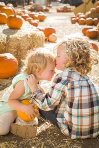 Sweet Little Boy Kisses His Baby Sister in a Rustic Ranch Setting at the Pumpkin Patch.