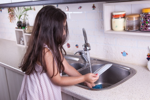 One beautiful middle eastern little girl with pink dress and long dark brown hair and eyes on white kitchen,helping parents to wash dishes and drinking water and smiling looking at camera studio.
