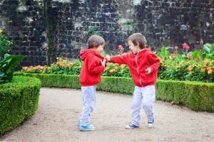 Two kids, boy brothers, fighting in garden, summertime rainy day