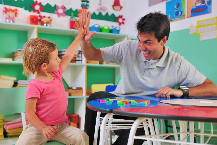 preschool teacher and child giving high-five