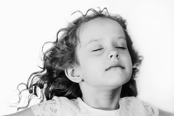 Little girl closed her eyes and breathes the fresh air. Black an