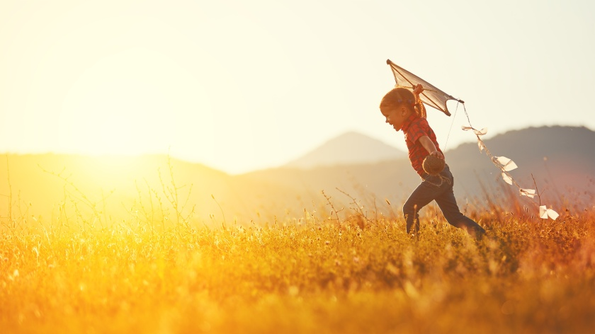 happy child girl with a kite running on meadow in summer