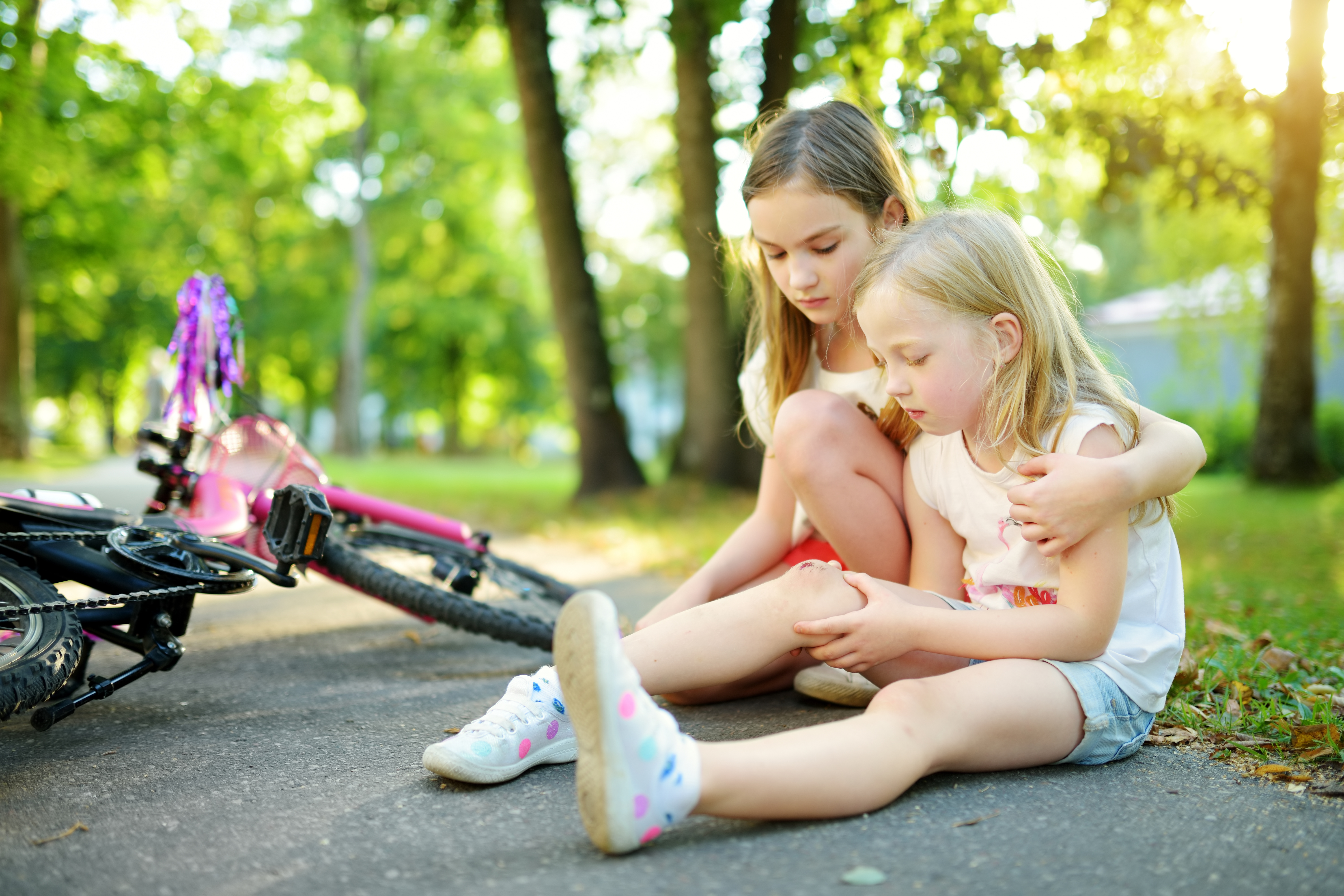 Adorable girl comforting her little sister after she fell off her bike at summer park. Child getting hurt while riding a bicycle.